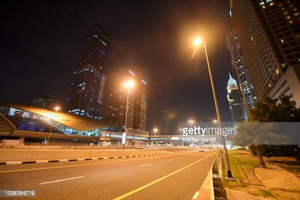 Picture taken on March 26 shows an empty road ahead of a curfew amid the coronavirus COVID-19 pandemic in Dubai. - Dubai closed its famous malls and...