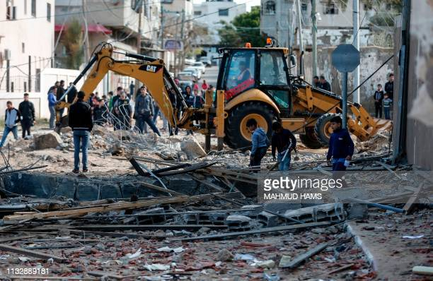 Picture taken on March 26 shows an excavator clearing debris next to the destroyed office of Hamas leader in Gaza City, Ismail Haniya, that was...