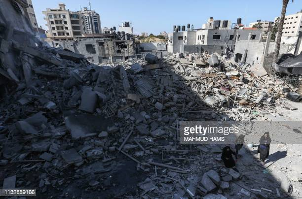 TOPSHOT A picture taken on March 26 shows Palestinians gathering next to the rubble of a building in Gaza City after Israeli air strikes hit dozens...