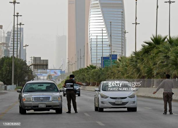 Picture taken on March 26 shows Saudi policemen manning a checkpoint on King Fahd road in the capital Riyadh, after the Kingdom began implementing an...