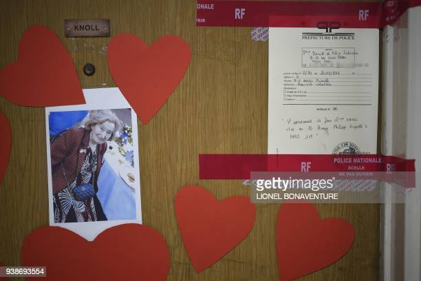 A picture taken on March 27 2018 shows a picture of Mireille Knoll heartshaped documents and seals of the police posted on the door of her apartment...
