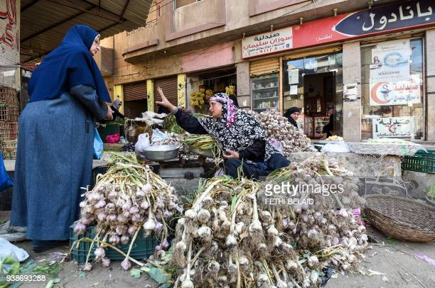 A picture taken on March 27 2018 shows an Egyptian garlic peddlar haggling with a customer as she sits by her produce at a market in the Nile Delta...