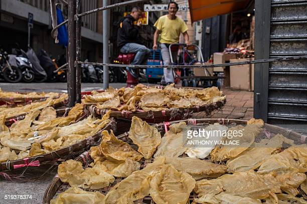 Picture taken on March 29 showing fish maws placed in a basket to dry on the side of a main road outside a dried goods shop in Hong Kong Mexico is...