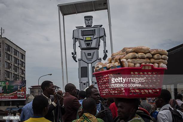 A picture taken on March 3 2015 in Kinshasa shows people attending the presentation ceremony of three new humanlike robots that were recently...