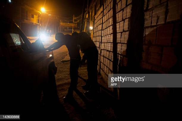 Picture taken on March 30 2012 showing a Venezuelan policeman frisking a man in Petare shantytown in Caracas According to the UN Caracas is the South...
