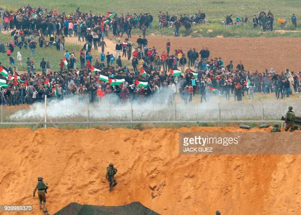 A picture taken on March 30 2018 from the southern Israeli kibbutz of Nahal Oz across the border from the Gaza strip shows Palestinians participating...