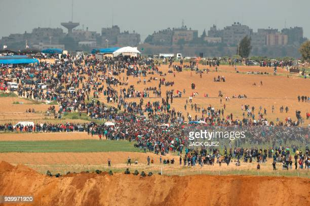 TOPSHOT A picture taken on March 30 2018 from the southern Israeli kibbutz of Nahal Oz across the border from the Gaza strip shows Palestinians...