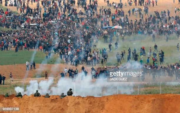 TOPSHOT A picture taken on March 30 2018 from the southern Israeli kibbutz of Nahal Oz across the border from the Gaza strip shows tear gas grenades...