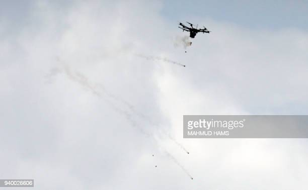 A picture taken on March 30 2018 shows an Israeli border police drone dropping tear gas canisters during clashes with Palestinian protesters...