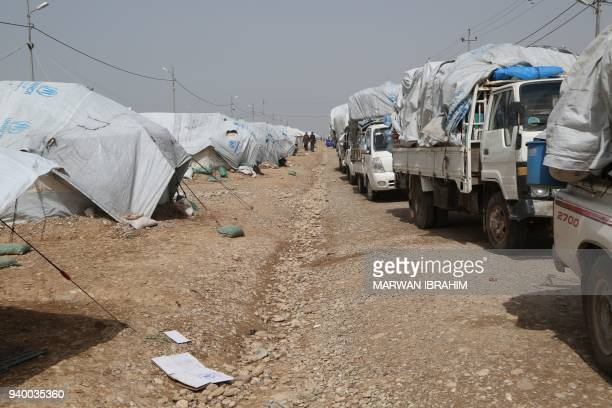 A picture taken on March 30 2018 shows Iraqi governmenthired trucks waiting to return home civilians who were displaced from the Hawija region during...