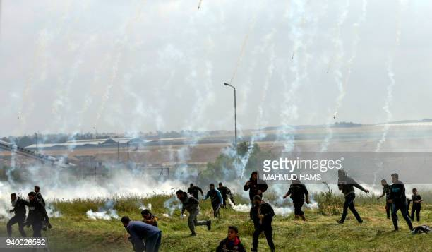TOPSHOT A picture taken on March 30 2018 shows Palestinians fleeing as tear gas grenades begin to drop during a demonstration near the border with...