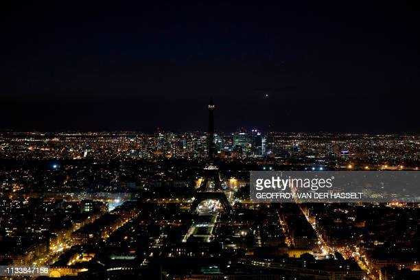 Picture taken on March 30, 2019 shows the Eiffel Tower, in Paris, switched-off during the a Earth Hour organised by the green group WWF. - Earth Hour...