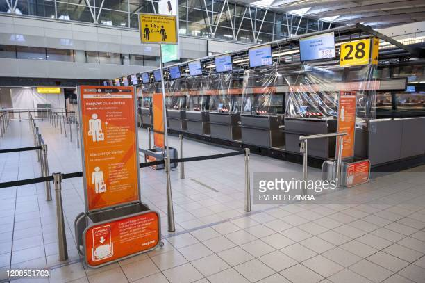 A picture taken on March 30 2020 at Schiphol airport shows the easyJet checkin counters British airline easyJet on March 30 2020 said it had grounded...