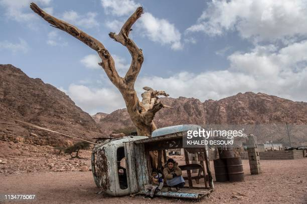 TOPSHOT A picture taken on March 30 shows Egyptian Bedouin children sitting in a rusted shell of a truck in the village of alHamada in Wadi elSahu in...
