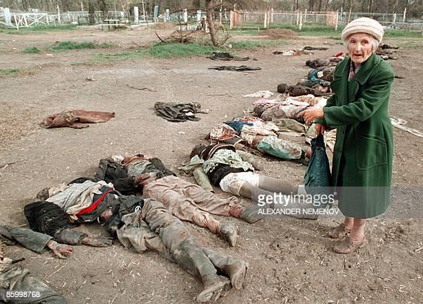Picture taken on March 31 1995 shows an elderly Russian woman pointing to the body of her son who disappeared during a Russian air raid when he left...