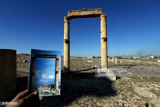 A picture taken on March 31 2016 shows a photographer holding his picture of the Temple of Baal Shamin seen through two Corinthian columns taken on...