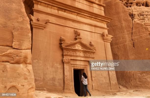 A picture taken on March 31 2018 shows a journalist taking a photo of a tomb at Madain Saleh a UNESCO World Heritage site near Saudi Arabia's...