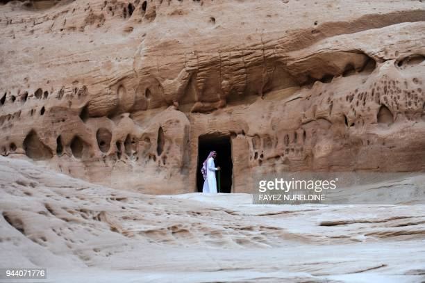 A picture taken on March 31 2018 shows a Saudi man standing at the entrance of a tomb at Madain Saleh a UNESCO World Heritage site near Saudi...