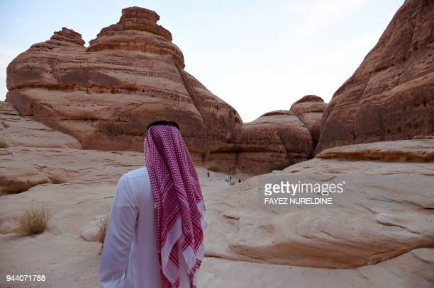 A picture taken on March 31 2018 shows a Saudi man walking between rosecoloured sandstone rocks in the Nabataean archaeological site near Saudi...
