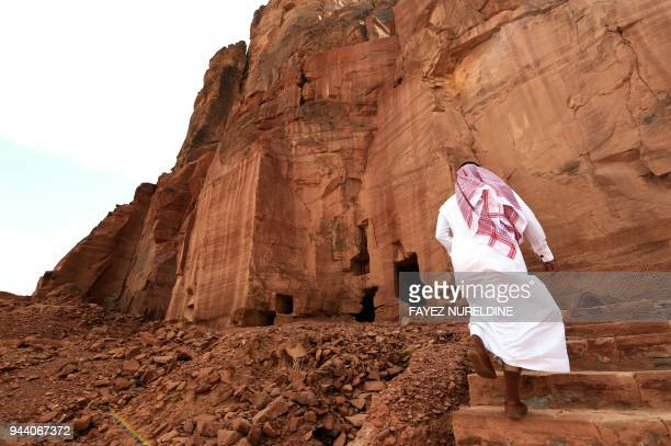 A picture taken on March 31 2018 shows a Saudi man walking near ancient tombs at the Khuraiba archaeological site near Saudi Arabia's northwestern...