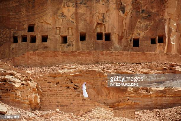 TOPSHOT A picture taken on March 31 2018 shows a Saudi man walking near ancient tombs at the Khuraiba archaeological site near Saudi Arabia's...