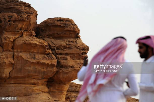 A picture taken on March 31 2018 shows Saudi men visiting the Khuraiba archaeological site near Saudi Arabia's northwestern town of alUla AlUla an...