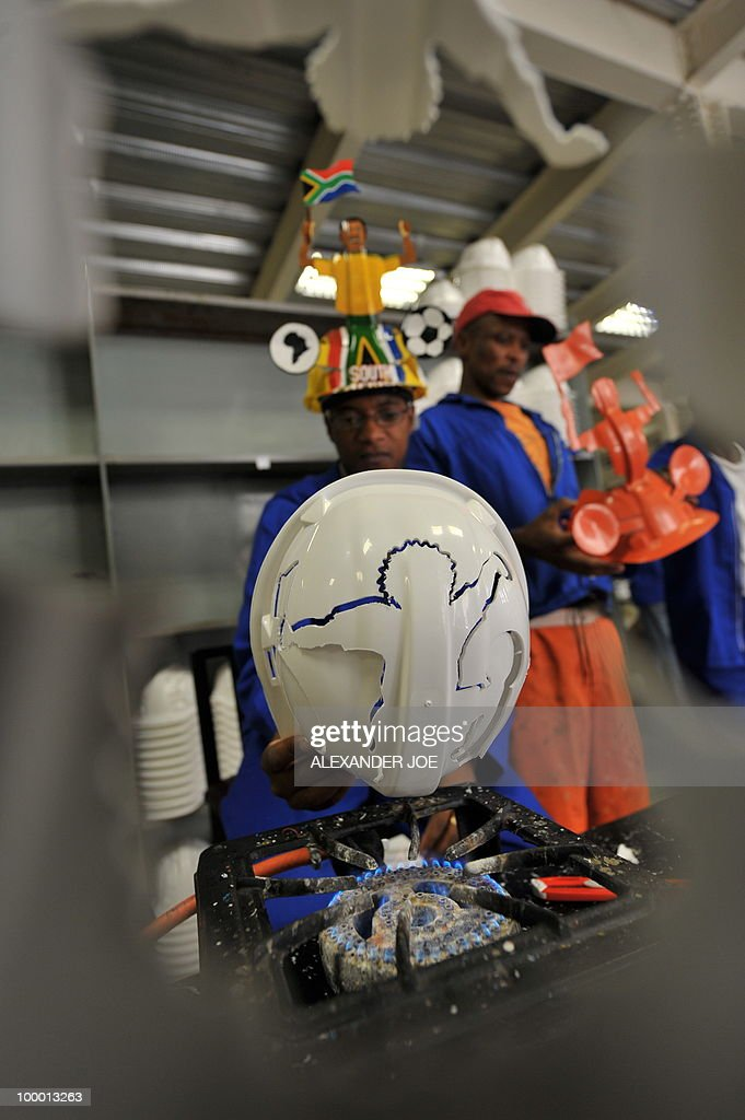 A picture taken on March 4, 2010 shows an employee displaying a football player on a hardhat known as 'Makarapas' in Johannesburg. The 'Makarapas', a decorated plastic hard hat due to be settled on supporters' heads, are created by fans who carve shapes into the hats and adorn them with team colours, a process that can take four days to complete. As the world prepares for Africa's first World Cup, interest is growing in the continent, especially since the governing body FIFA ordered 2,000 Makarapas for twelve of the top teams from Wygers' factory in downtown Johannesburg. The Makarapa is, with the vuvuzela trumpet, an important part of the local football matches' festival atmosphere. Makarapas are hand-cut and hand painted miner hard hats in the colours of a team.