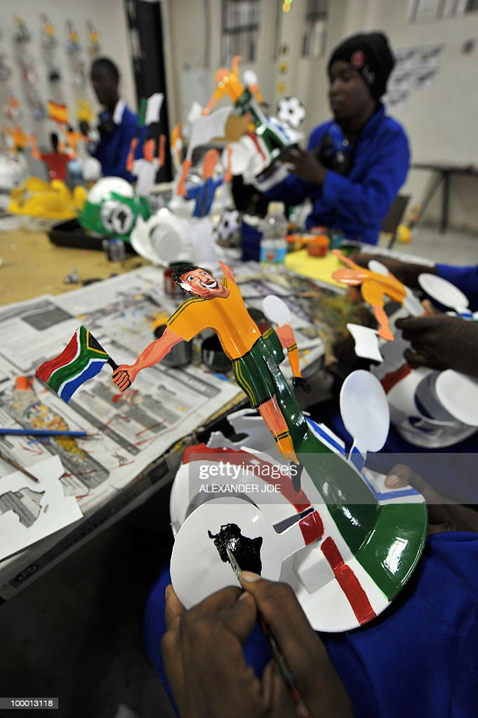 A picture taken on March 4, 2010 shows an employee preparing a football player on a hardhat known as 'Makarapas' in Johannesburg. The 'Makarapas', a decorated plastic hard hat due to be settled on supporters' heads, are created by fans who carve shapes into the hats and adorn them with team colours, a process that can take four days to complete. As the world prepares for Africa's first World Cup, interest is growing in the continent, especially since the governing body FIFA ordered 2,000 Makarapas for twelve of the top teams from Wygers' factory in downtown Johannesburg. The Makarapa is, with the vuvuzela trumpet, an important part of the local football matches' festival atmosphere. Makarapas are hand-cut and hand painted miner hard hats in the colours of a team.