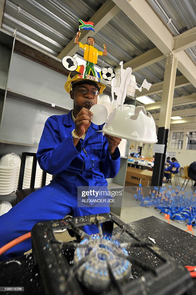 A picture taken on March 4, 2010 shows an employee preparing a football player on a hardhat known as 'Makarapas' in Johannesburg. The 'Makarapas', due to be settled on supporters' heads, are created by fans who carve shapes into the hats and adorn them with team colours, a process that can take four days to complete. As the world prepares for Africa's first World Cup, interest is growing in the continent, especially since the governing body FIFA ordered 2,000 Makarapas for twelve of the top teams from Wygers' factory in downtown Johannesburg. The Makarapa is, with the vuvuzela trumpet, an important part of the local football matches' festival atmosphere. Makarapas are hand-cut and hand painted miner hard hats in the colours of a team.