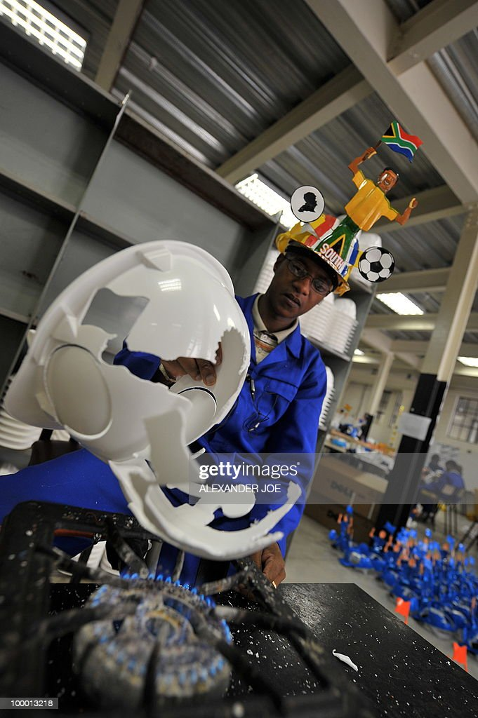 A picture taken on March 4, 2010 shows an employee preparing a hardhat known as 'Makarapas' in Johannesburg. The 'Makarapas', a decorated plastic hard hat due to be settled on supporters' heads, are created by fans who carve shapes into the hats and adorn them with team colours, a process that can take four days to complete. As the world prepares for Africa's first World Cup, interest is growing in the continent, especially since the governing body FIFA ordered 2,000 Makarapas for twelve of the top teams from Wygers' factory in downtown Johannesburg. The Makarapa is, with the vuvuzela trumpet, an important part of the local football matches' festival atmosphere. Makarapas are hand-cut and hand painted miner hard hats in the colours of a team.