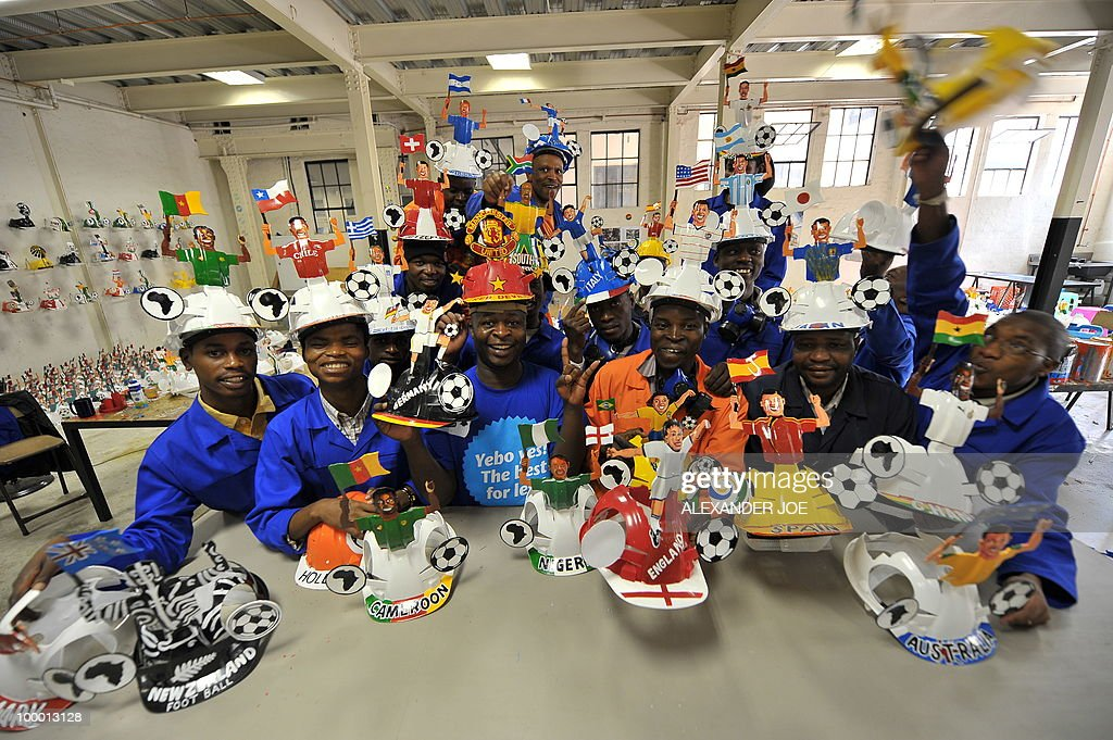 A picture taken on March 4, 2010 showsemployees displaying football player hardhats known as 'Makarapas' in Johannesburg. The 'Makarapas', a decorated plastic hard hat due to be settled on supporters' heads, are created by fans who carve shapes into the hats and adorn them with team colours, a process that can take four days to complete. As the world prepares for Africa's first World Cup, interest is growing in the continent, especially since the governing body FIFA ordered 2,000 Makarapas for twelve of the top teams from Wygers' factory in downtown Johannesburg. The Makarapa is, with the vuvuzela trumpet, an important part of the local football matches' festival atmosphere. Makarapas are hand-cut and hand painted miner hard hats in the colours of a team.
