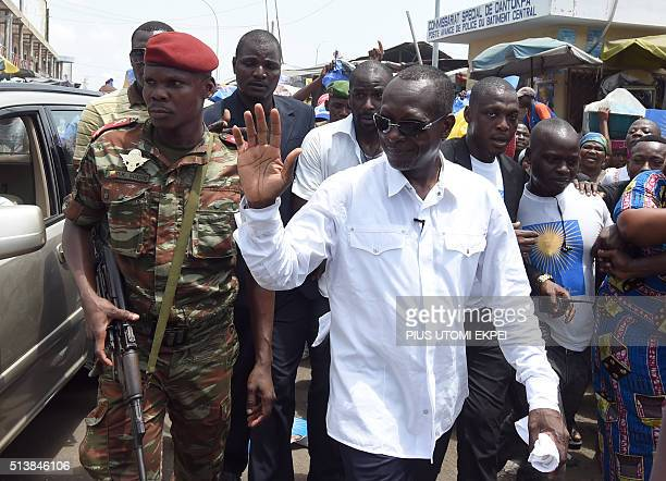 A picture taken on March 4 2016 shows cotton tycoon and presidential candidate Patrice Talon flanked by supporters waving during a rally in Cotonou...