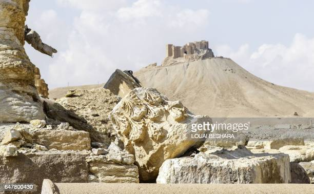 Picture taken on March 4, 2017 shows a fallen column capital at the site of the ancient city of Plamyra in central Syria, with the Fakhr-al-Din...