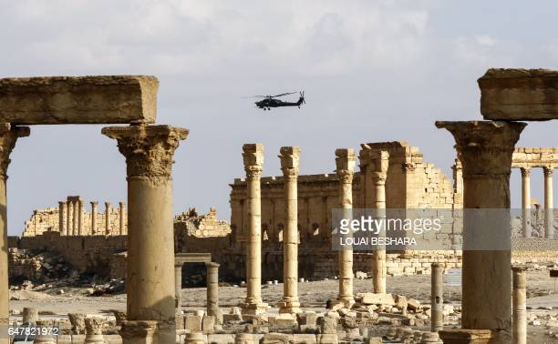 """Picture taken on March 4, 2017 shows a Mil Mi-28 """"Havoc"""" attack helicopter flying above the damaged site of the ancient city of Palmyra in central..."""