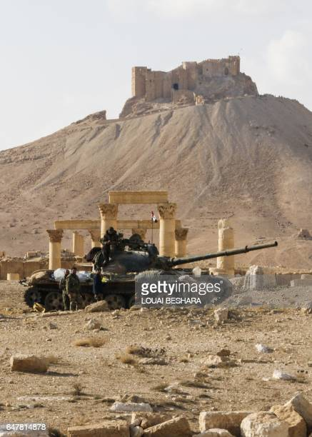 A picture taken on March 4 2017 shows a Syrian army T62 tank at the damaged site of the ancient city of Palmyra in central Syria with the FakhralDin...