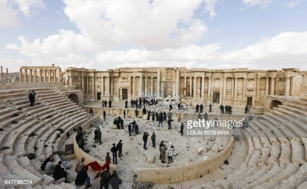 TOPSHOT A picture taken on March 4 2017 shows journalists at the site of the damaged Roman amphitheatre in the ancient city of Palmyra in central...