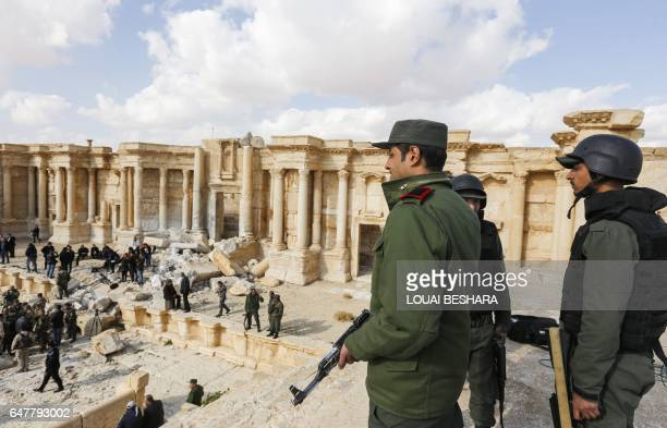 A picture taken on March 4 2017 shows Syrian soldiers standing guard at the site of the damaged Roman amphitheatre in the ancient city of Palmyra in...