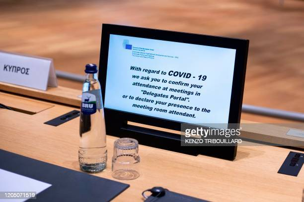 A picture taken on March 4 2020 shows a screen with an alert message about COVID19 outbreak ahead of a Justice and Home Affairs Council at the...