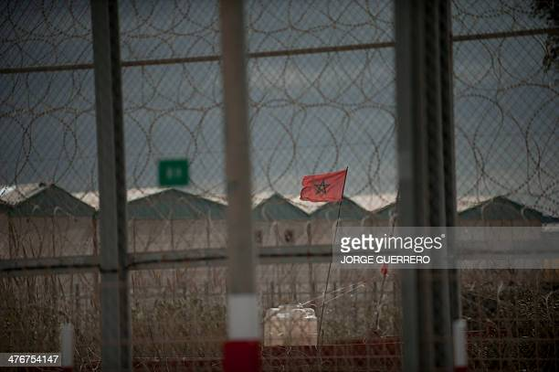 A picture taken on March 5 2014 shows a Moroccan flag flying behind the border fence between Morocco and Spain during a visit of Spain's Interior...