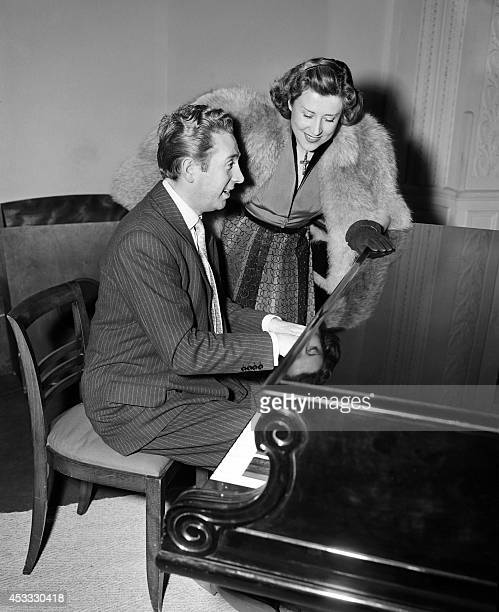 A picture taken on March 6 1952 shows French singers Yvette Giraud with Charles Trenet at the piano during a reception given by the company...