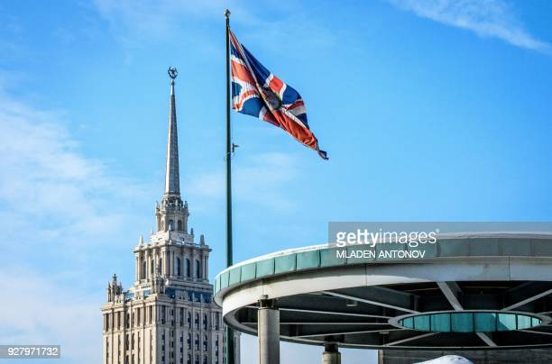 A picture taken on March 6 2018 shows the United Kingdom flag flying in the wind outside its embassy with a Stalinera skyscraper seen in the...