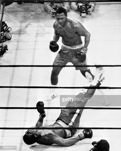 A picture taken on March 8 1971 shows US heavyweight boxing champion Joe Frazier keeping his title at the end of the fight called the match of the...
