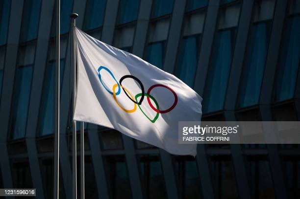 Picture taken on March 8, 2021 in Lausanne shows the Olympic flag floating next to the headquarters of the International Olympic Committee ahead of a...