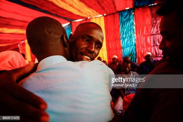 A picture taken on March 9 2017 shows a prisoner who was released from the Sudanese Cooper prison north of the capital Khartoum being hugged during a...