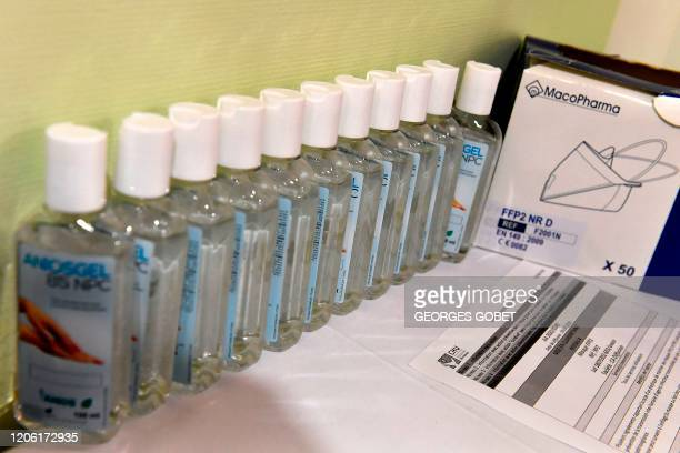 A picture taken on March 9 2020 shows bottles of alcohol gel hand sanitiser past a box with an FFP2 protective face mask at the hospital screening...
