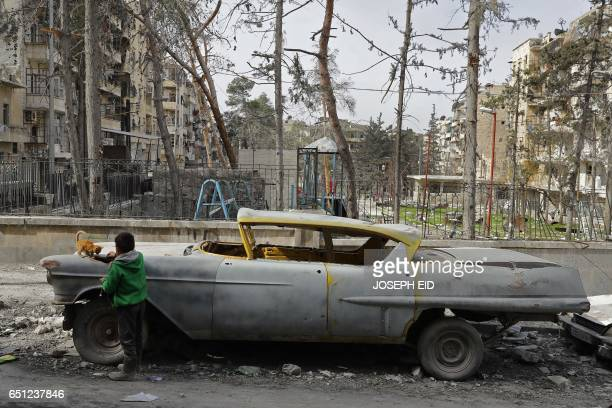 A picture taken on March 9 shows a boy playing with a cat next to a 1948 Buick parked outside the home of Mohammad Mohiedine Anis in the formerly...
