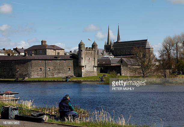 A picture taken on May 1 2013 shows a man fishing in the shadow of Enniskillen Castle in Enniskillen County Fermanagh Northern Ireland near the venue...