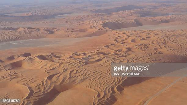 A picture taken on May 10 2016 from a Saudi Aramco passenger airplane shows sand dunes near the Shaybah oilfield some 800 kilometers southeast of the...