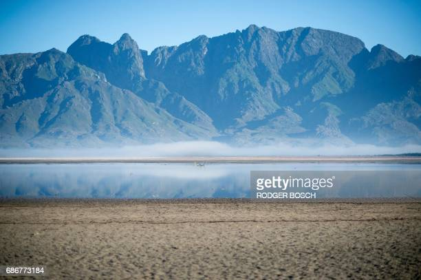 TOPSHOT A picture taken on May 10 2017 shows bare sand and a narrow body of water facing the sky at Theewaterskloof Dam which has less than 20% of...