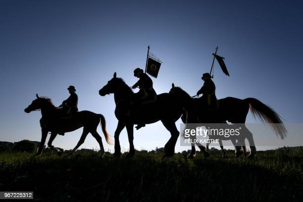 TOPSHOT A picture taken on May 11 2018 in Weingarten southern Germany shows the silhouettes of horse riders during the traditional Holy Blood...